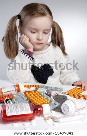 Contemplating little girl behind pile of medications