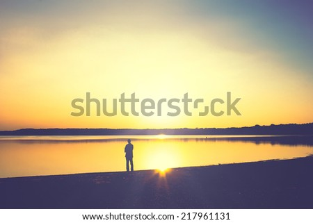Contemplation at the Lakeshore, looking at the sunset - stock photo