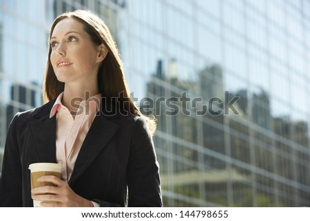 Contemplative female office worker with drink outside office building - stock photo