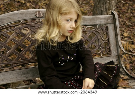 Contemplative girl on a bench - stock photo