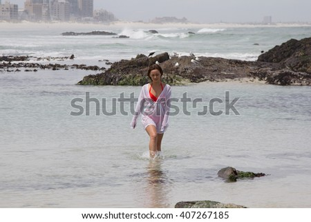 Contemplative woman in shirt and bikini taking a dip in the sea by the shore with copyspace