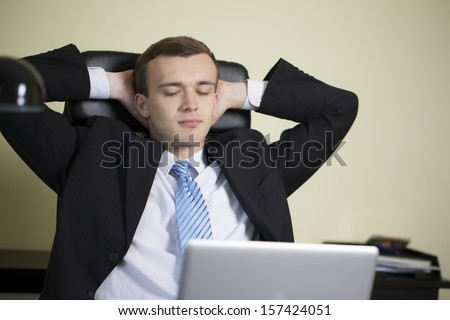 Contemplative young businessman taking a break at work - stock photo