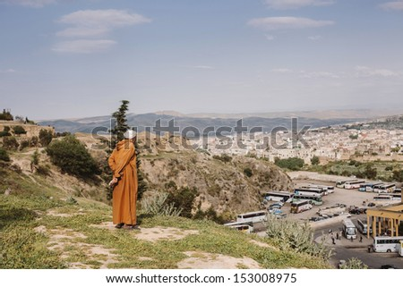 Contemplator, old man looking at the panorama of Fes, Morocco - stock photo
