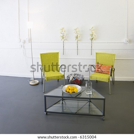 Contemporary arm chairs and coffee table inside room. - stock photo