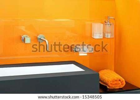 Contemporary bathroom basin with vivid orange wall - stock photo