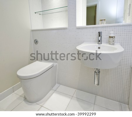 contemporary bathroom with mosaic tiles and white ceramic appliances - stock photo