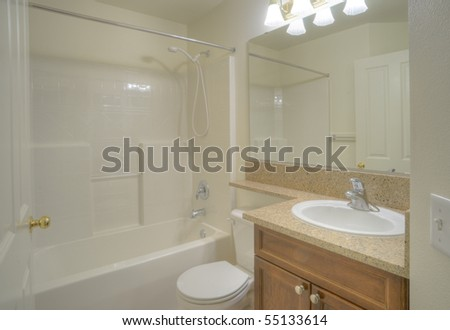 Contemporary bathroom with stone counter and large mirror