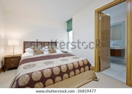 contemporary bedroom with open door to en-suite bathroom - stock photo