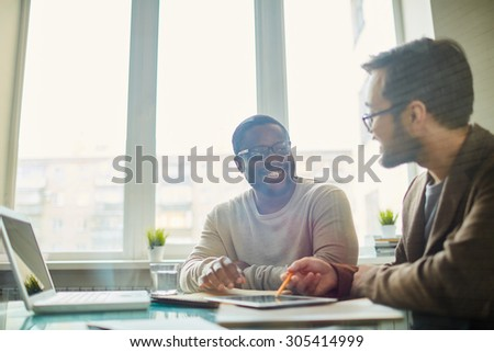 Contemporary businessmen interacting at meeting - stock photo