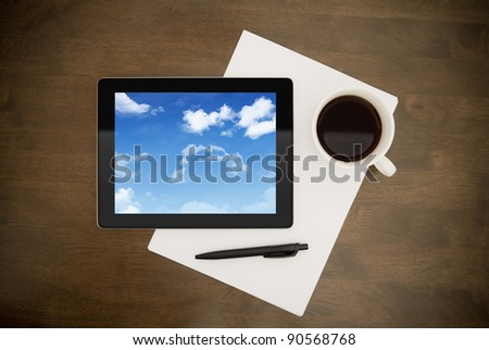 Contemporary digital tablet with cloudy sky on screen lying on worktable with paper, pen and cup of coffee. Concept image on cloud-computing theme. Directly above view. - stock photo