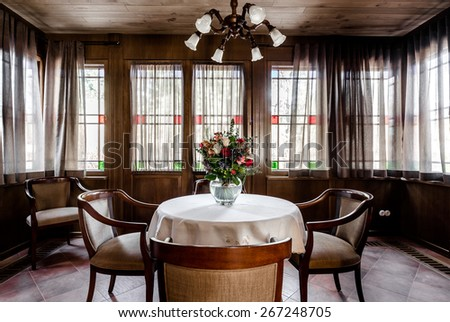 Contemporary dining room design. Glassed room with wooden ceiling, comfortable chairs, round table with white tablecloth and bouquet of flowers - stock photo