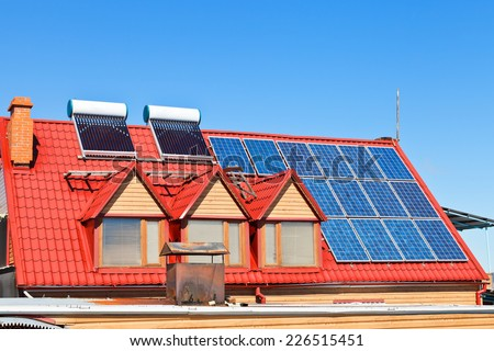 contemporary energy-saving technology - Solar Batteries and heaters on home roof - stock photo