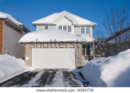 contemporary 2 floor beige brick house with garage in front; heavy snow; driveway in foreground; frontal view; deep blue sky - stock photo