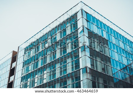 Contemporary glass and steel building in urban setting under a grey sky