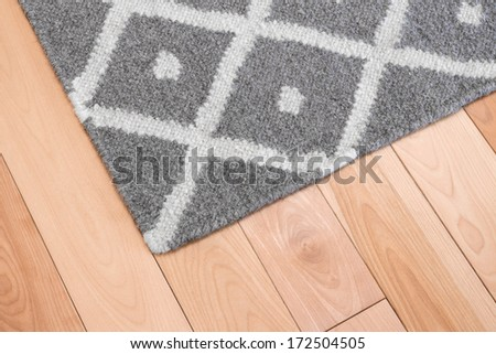 Contemporary gray wool rug on wooden floor. - stock photo