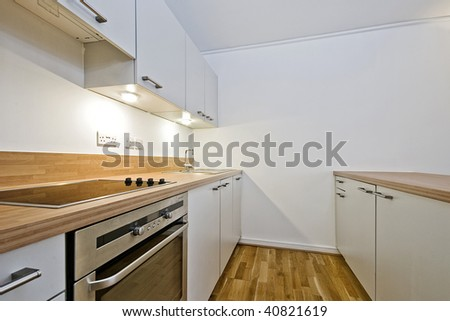 contemporary kitchen in white with wooden worktop - stock photo