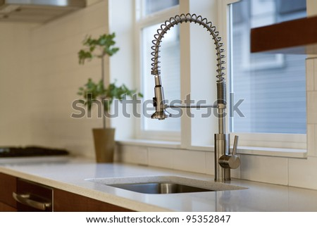 Contemporary Kitchen with Chrome Fixture and white conter tops - stock photo