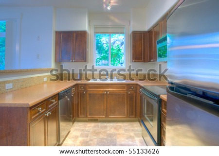 Contemporary kitchen with stainless steel appliances and granite backsplash - stock photo