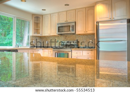 Contemporary kitchen with stainless steel appliances reflecting in granite countertop - stock photo