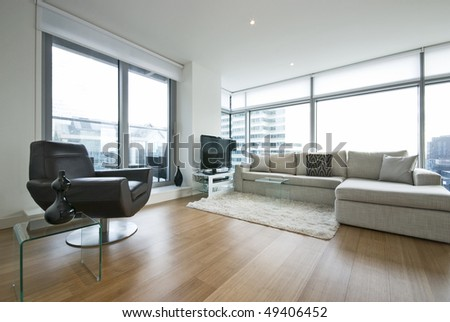 Contemporary living room with designer furniture, floor to ceiling windows and panoramatic views - stock photo