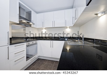 contemporary luxury kitchen in white with black stone worktop - stock photo