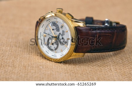 Contemporary men's luxury wrist watch isolated on light color fabric background. - stock photo