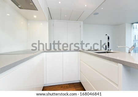 Contemporary modern fully fitted kitchen in white with top spec appliances and granite worktops - stock photo