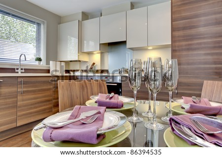 Contemporary modern kitchen with table in the foreground dressed for dining with plates, bowls, serviettes, cutlery and wine glasses - stock photo
