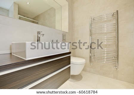 Contemporary modern tiled bathroom with chrome plated towel rail, wc, sink and cabinet.