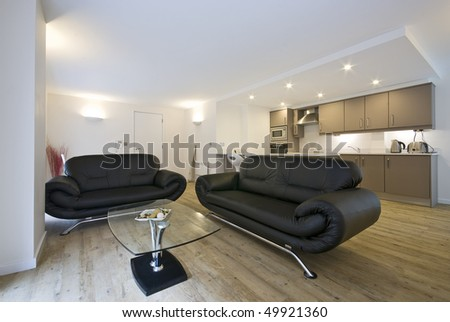 Contemporary open plan living area with large leather sofa, fully fitted kitchen and dining area - stock photo