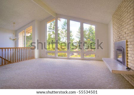 Contemporary room with fireplace cathedral ceilings and panoramic windows - stock photo