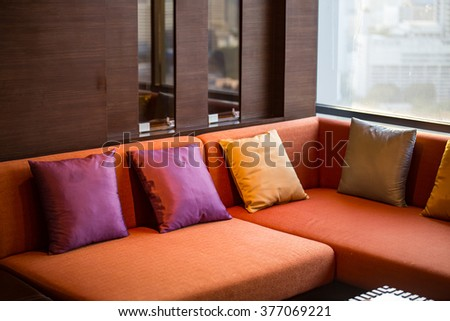 contemporary sofa and pillows near windows warm lighting