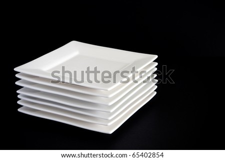 Contemporary square white plates stacked against a dark black background - stock photo