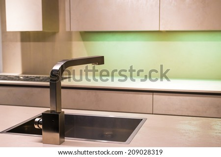 Contemporary Stainless Steel Tap in Minimalist Kitchen - stock photo