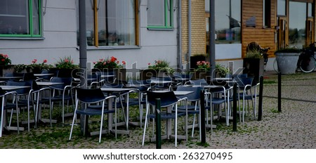 Contemporary Street Cafe with Steel Tables and Black Chairs on Paving Stone in Malmo, Sweden - stock photo