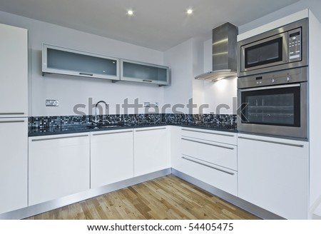contemporary white kitchen with built in appliances and mosaic tiles - stock photo