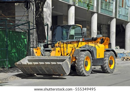 Contemporary yellow bulldozer near building construction site