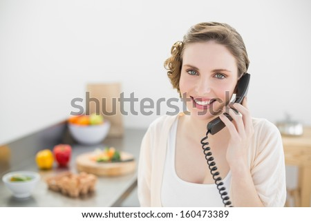 Content beautiful woman phoning in her kitchen with a telephone smiling at camera - stock photo