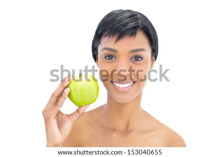 Content black haired woman holding an apple on white background - stock photo