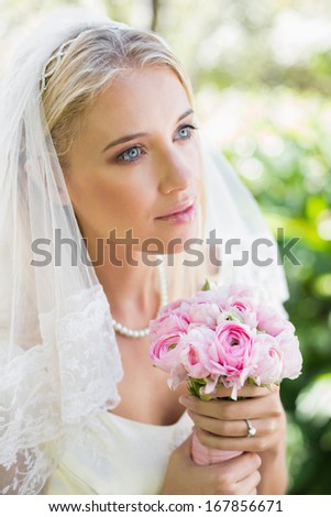 Content bride wearing veil holding bouquet looking away in the countryside