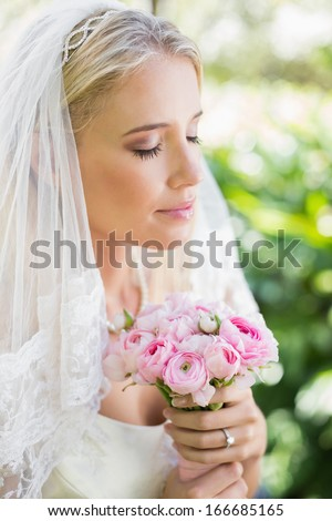 Content bride wearing veil holding bouquet with eyes closed in the countryside