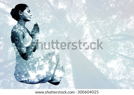 Content brunette in white sitting in lotus pose against low angle view of tall trees - stock photo