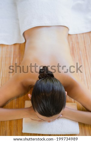 Content brunette relaxing on massage table at the health spa