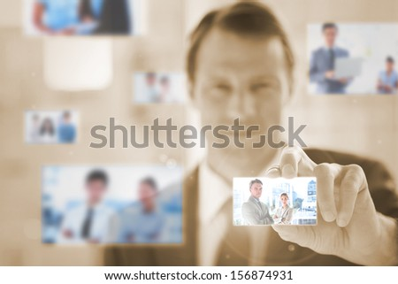Content businessman picking a picture on sepia background - stock photo