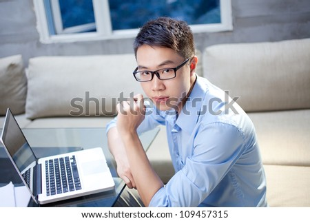 Content businessman sitting at his workplace with laptop and looking at camera