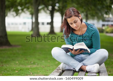 Content casual student sitting on bench reading on campus at college - stock photo