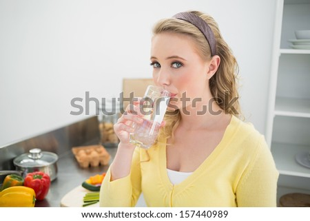 Content cute blonde drinking a glass of water in bright kitchen - stock photo