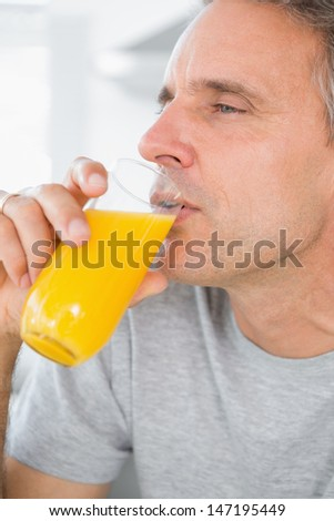 Content man drinking orange juice in kitchen at home