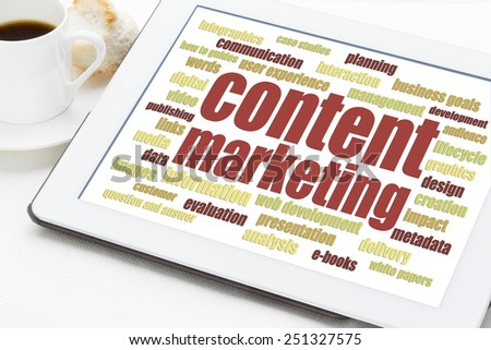 content marketing word cloud on a digital tablet with a cup of coffee - stock photo