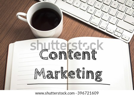 Content marketing written on notebook , keyboard and coffee on wood table - stock photo